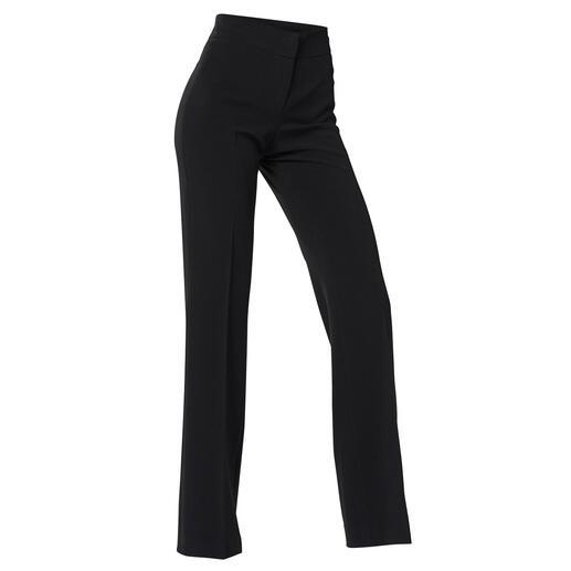 Het zakelijke type onder de broeken met modieus wijde pijpen. Het zakelijke type onder de broeken met modieus wijde pijpen. Serieus model. Chique stof. Klassiek zwart.